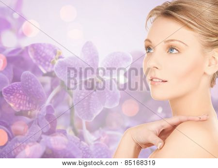 beauty, people and health concept - beautiful young woman touching bare shoulder over purple orchid flowers background