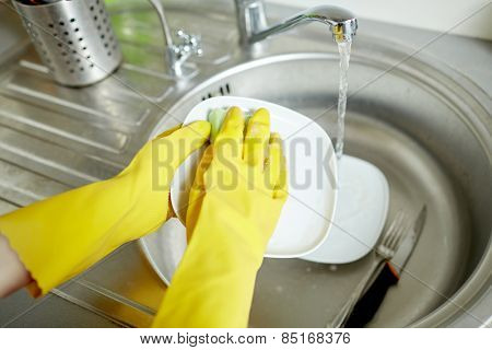 people, housework, washing-up and housekeeping concept - close up of woman hands in protective gloves washing dishes with sponge at home kitchen