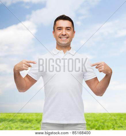 happiness, advertisement, fashion, gesture and people concept - smiling man in t-shirt pointing fingers on himself over blue sky and grass background