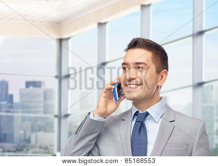 business, people and technology concept -happy businessman calling on smartphone over office room and window with city view background
