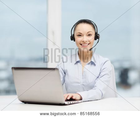 business, communication and call center concept - friendly female helpline operator with headphones and laptop computer