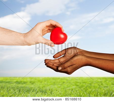 love, charity, valentines day, donation and international concept - close up of man hand giving heart to woman over blue sky and grass background
