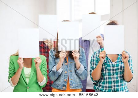 education concept - group of students covering faces with blank papers