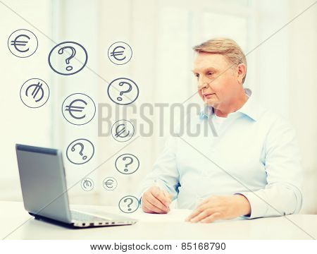 business, tax and office concept - old man with laptop filling a form at home