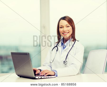 medicine and healthcare concept - busy doctor with laptop computer