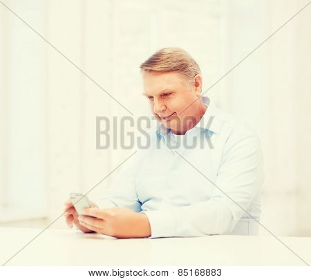 oldness, new technology, office and happiness concept - old man at home with smartphone