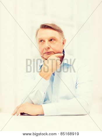 oldness, business and people concept - stressed old man holding head at home