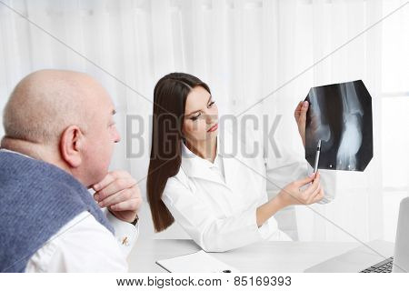 Doctors receiving X-ray results in office on white background