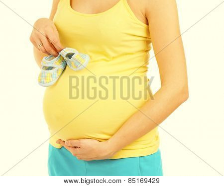 Beautiful young pregnant woman with baby boots on light background