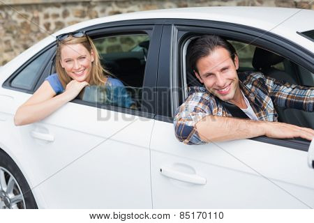Couple smiling at the camera in their car