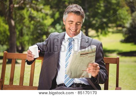 Businessman reading newspaper in the park on a sunny day