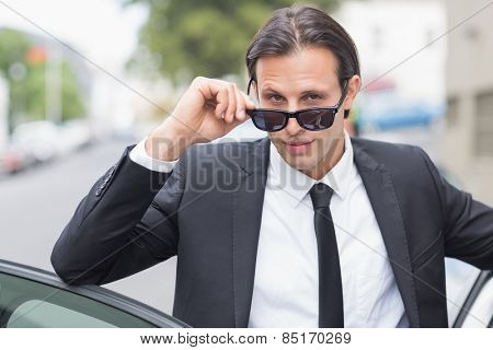 Businessman looking at the camera outside his car