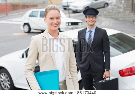 Businesswoman and her chauffeur smiling at camera outside the car