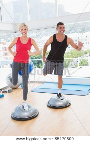 Fit couple working on bosu ball in fitness studio