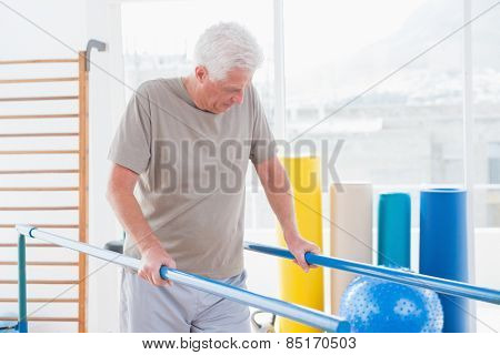 Senior man walking with parallel bars in fitness studio
