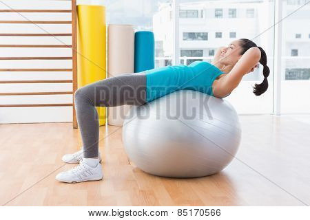 Woman exercising on fitness ball in fitness studio