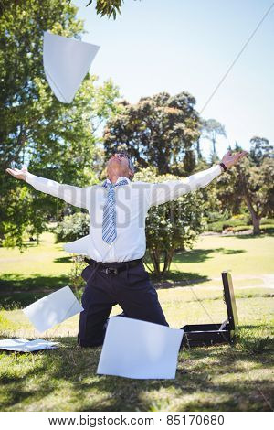 Businessman tossing papers in the park on a sunny day