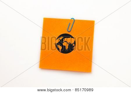 Earth against orange adhesive note with a paperclip