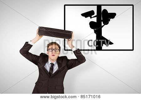 Young geeky businessman holding briefcase against cctv