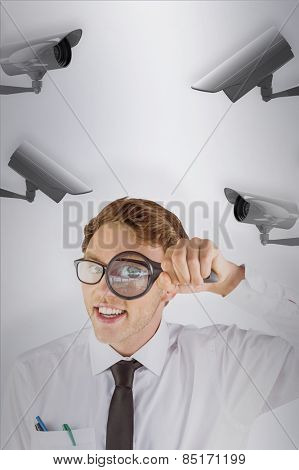 Geeky businessman looking through magnifying glass against cctv camera
