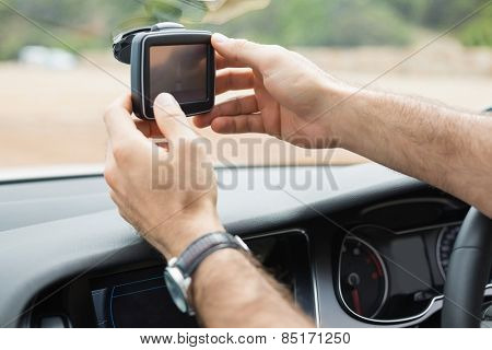 Man using satellite navigation system in his car