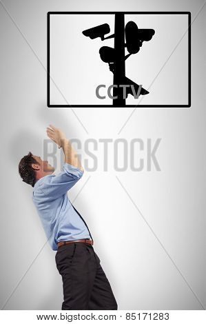 Businessman posing with arms up against cctv