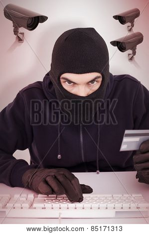 Concentrated burglar in balaclava shopping online against cctv camera
