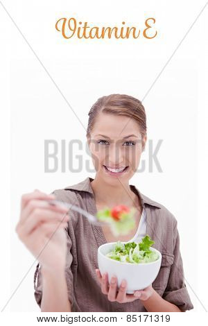 The word vitamin e against woman with bowl of salad offering some