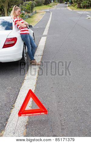 Annoyed young woman beside her broken down car in the street
