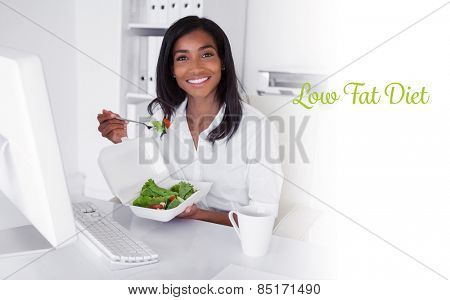 The word low fat diet against happy pretty businesswoman eating a salad at her desk
