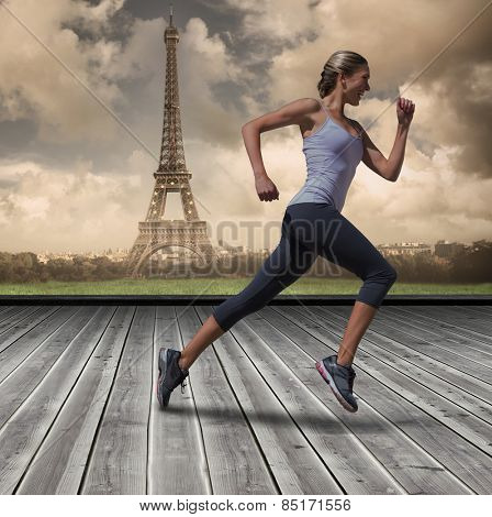 Pretty fit blonde jogging against wooden planks against paris