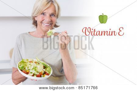The word vitamin e against smiling woman eating salad