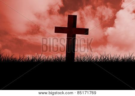 Wooden cross against red sky over grass