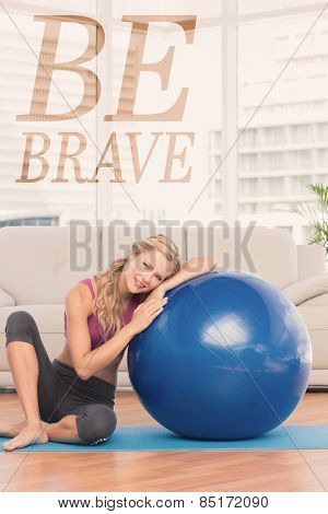 Fit blonde sitting beside exercise ball smiling at camera against be brave