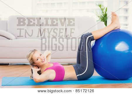 Cheerful fit blonde doing sit ups with exercise ball against believe in myself