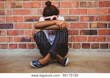 Full length of tensed girl sitting against brick wall in school corridor