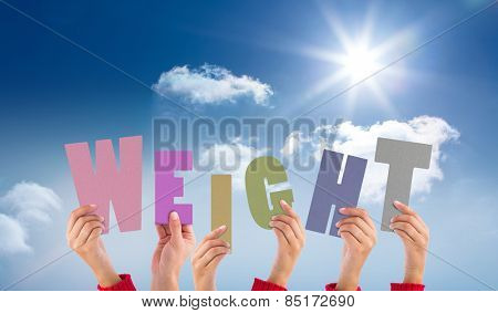Hands holding up weight against bright blue sky with clouds