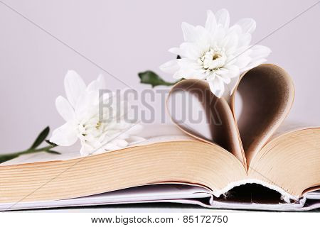 Open book with shape of heart from pages and flowers on light background