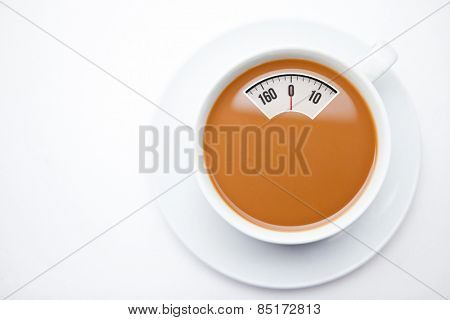 weighing scales against cup of coffee with milk