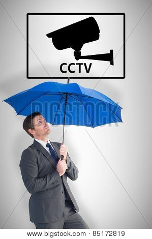 Businessman sheltering under blue umbrella against cctv