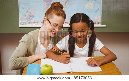 Portrait of teacher assisting little girl with homework in the classroom