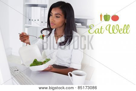 The word eat well against pretty businesswoman eating a salad at her desk
