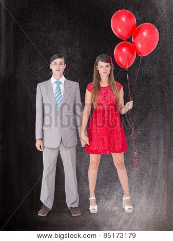 Unsmiling geeky couple standing hand in hand against black background