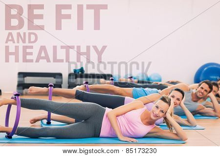 Sporty people with exercising rings in fitness studio against be fit and healthy