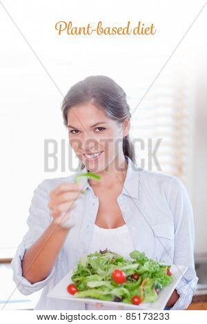 The word plant-based diet against portrait of a happy woman eating a salad