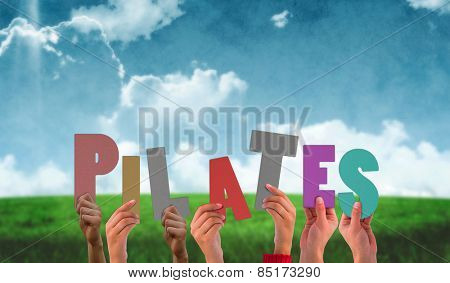 Hands holding up pilates against blue sky over green field