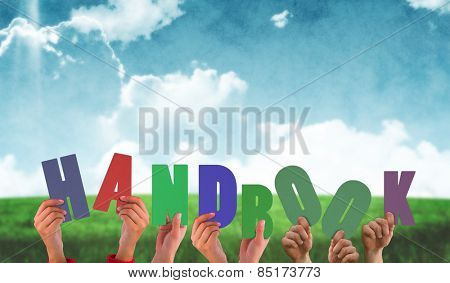 Hands holding up handbook against blue sky over green field