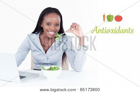 The word antioxidants against cute businesswoman working with a notebook while eating a salad