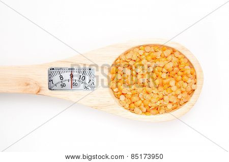 weighing scales against wooden spoon with lentils