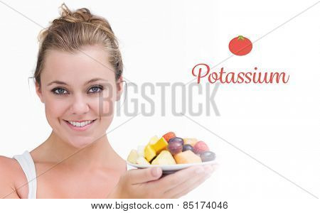 The word potassium against woman holding up a plate fruits